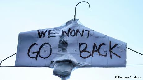 Abortion rights campaigners at a New York rally hold up a wire coat hanger covered with the message: We won't go back