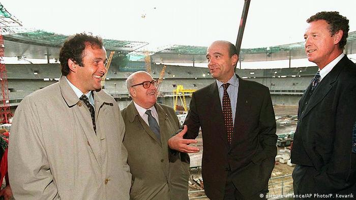 World Cup '98 organization committee co-presidents Michel Platini, left, and Fernand Sastre, second left, tour the Stade de France building site with Prime Minister Alain Juppe, second from right, and sports minister Guy Drut in Saint-Denis outside Paris Tuesday May 20, 1997. (picture-alliance/AP Photo/P. Kovarik)