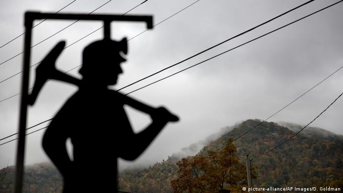 A fog hovers over a mountaintop as a cut out of a coal miner stands at a memorial to local miners in Kentucky