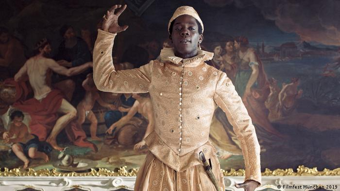 Black man in white theatrical garb before the backdrop of a historic painting in a still from Angelo (Filmfest München 2019)