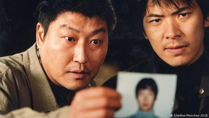 Szene aus Bong Joon Hos Memories of a Murder mit zwei Männern, die sich ein Passfoto anschauen