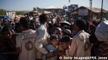 Rohingya Muslim refugees children queue for aid suplies at the Kutupalong refugee camp in Cox's Bazar on December 4, 2017