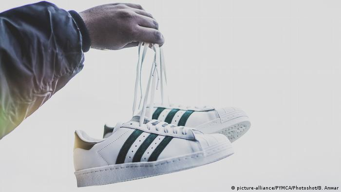 c450971d8 A man holds up a pair of Adidas shoes with its three-stripes trademark