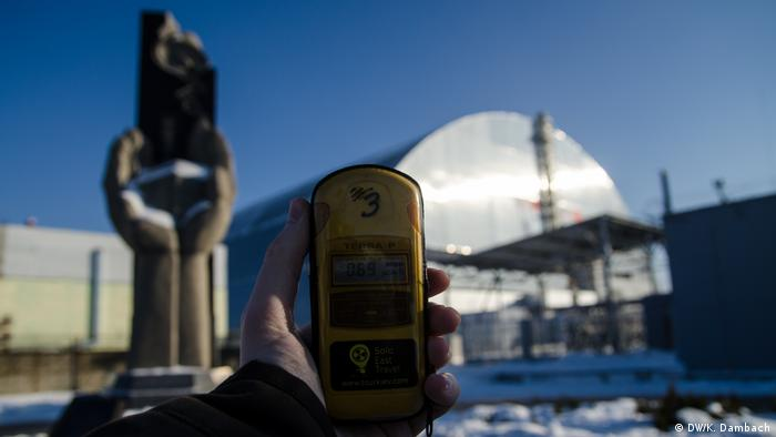 Hand holding a Geiger counter with the Chernobyl sarcophagus covered reactor in the background, Ukraine
