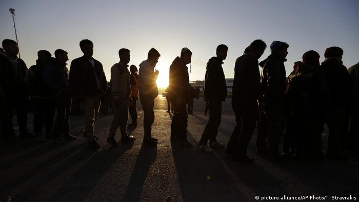 Refugees and migrants wait in a queue as the sun rises