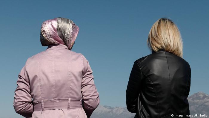 Frau mit islamischem Mantel und Kopftuch sowie blonde Frau mit schwarzer Lederjacke von hinten fotografiert, vor blauem Himmel und Bergkulisse