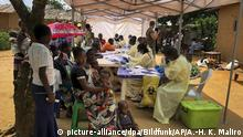 17.06.2019, Kongo, Mabalako: Eine Frau und ihre Kinder warten auf ihre Ebola-Impfungen. Zur Zeit terrorisieren rivalisierende Gruppen den Osten Kongos mit Schießereien, Entführungen, Vergewaltigungen und Verstümmelungen. Dadurch sind in der Provinz Ituri innerhalb von zwei Wochen 300 000 Menschen vertrieben worden, wie das UN-Flüchtlingshilfswerk UNHCRberichtete. Gefährlich ist die Lage vor allem, weil es in der Provinz schon zahlreiche Fälle der hochansteckenden Viruskrankheit Ebola gegeben hat. Foto: Al-Hadji Kudra Maliro/AP/dpa +++ dpa-Bildfunk +++ |