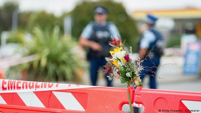 Flowers are seen in front of a police cordon at Linwood mosque