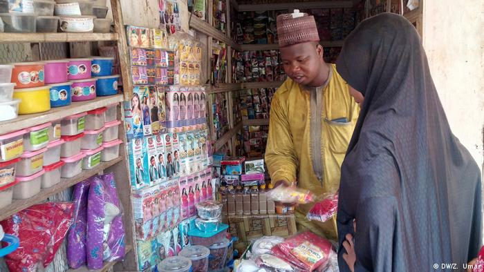 A shop owner sells items to a woman