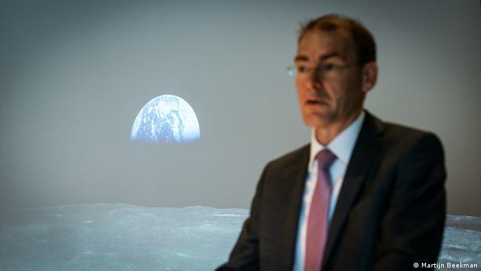 Menno Snel speaks in fron of a screen showing the earth