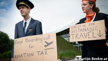 Two people dressed in uniforms of plane staff hold up signs for greener plane travel (Martijn Beekman)
