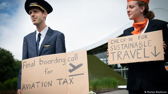 Two people dressed in uniforms of plane staff hold up signs for greener plane travel