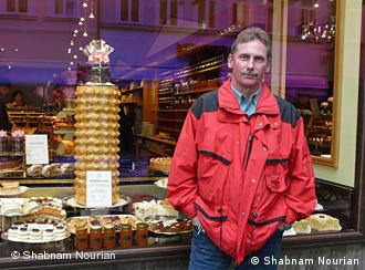 Bernd standing outside a shop window display of cakes