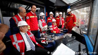 Various people stand in red jackets while inspecting the ship Yavuz