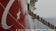 People walk off the gangplank of the ship Yavuz, which features a large Turkish flag on its side (picture-alliance/dpa/Bildfunk/AP/L. Pitarakis)
