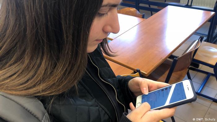 Ioanna Kakymota scrolls through her phone on a school break