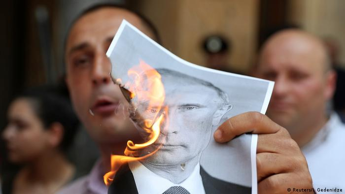 A protester burns a portrait of Putin