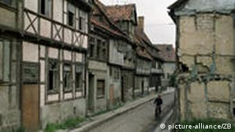 A cyclist in a street of dilapidated old half-timbered houses in Quedlinburg in the former East Germany, 1985. Photo: Heinz Junge(c) dpa