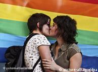 Дві лесбійки цілуються на фоні веселкового прапора у Ліссабоні