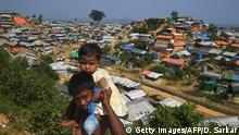 Young Rohingya refugees look on as a general view of Balukhali refugee camp is pictured in Ukhia on November 16, 2018. - Rohingya Muslims were fleeing Bangladeshi refugee camps to avoid being repatriated to Myanmar later this week, community leaders said on November 12. Authorities plan to begin returning Rohingya refugees, who have fled what the UN has called ethnic cleansing, to the Buddhist majority country from November 15. (Photo by Dibyangshu SARKAR / AFP) (Photo credit should read DIBYANGSHU SARKAR/AFP/Getty Images)