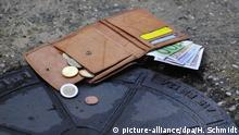 Verlorene Geldbörse auf Kanaldeckel