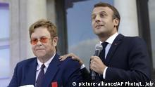 21.06.2019, Frankreich, Paris: Der französische Präsident Emmanuel Macron (r) und Sir Elton John sprechen im Innenhof des Elyseepalast. Frankreichs PräsidentMacron hat den britischen Popstar Elton John zum Ritter der Ehrenlegion gemacht. Damit werde die künstlerische Karriere und der Kampf des 72 Jahre alten Sängers gegen HIV und Aids gewürdigt, machte Macron am Freitagabend im Élyséepalast deutlich. Foto: Lewis Joly/AP/dpa +++ dpa-Bildfunk +++  