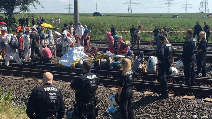Protesters and police stand either side of railway tracks
