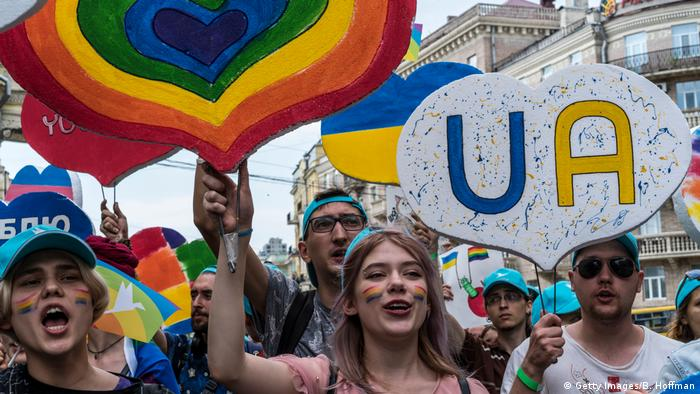 a group of people smiling and holding signs at the 2019 Pride march in Kyiv