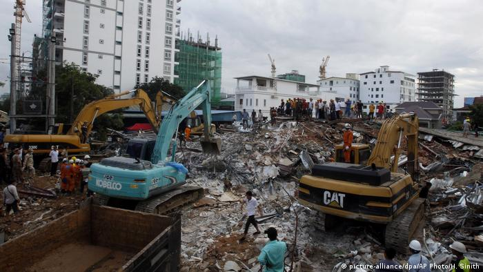 Rescuers use diggers to remove rubble