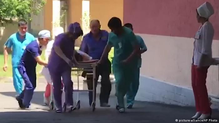 In this video grab provided by Radio Free Europe Kazakh Service medical personnel take an injured person into hospital in Arys, southern Kazakhstan