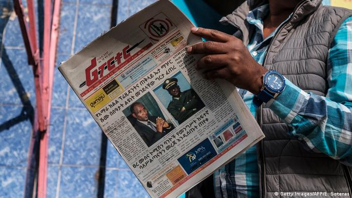 A man holds the Ethiopian newspaper 'The Reporter', depicting the portraits of killed Ambachew Mekonen (L), President of the Ahmara Region, and of Gen. Sere Mekonen, Chief of Staff of the Ethiopian National Forces, in Addis Ababa, on June 24, 2019.