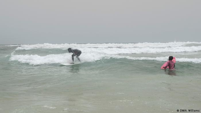 Senegalese surfers riding waves on the beach of Yoff, in Dakar, Senegal.