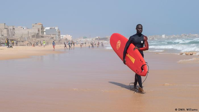 A surfer walking along the beach with a red board