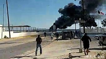 A still from camera footage showing scenes of fighting between Mexican fishermen and locals in the town of San Felipe. Thick black smoke can be seen in the background.