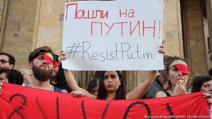 Georgian protesters holds placards in capital Tbilisi