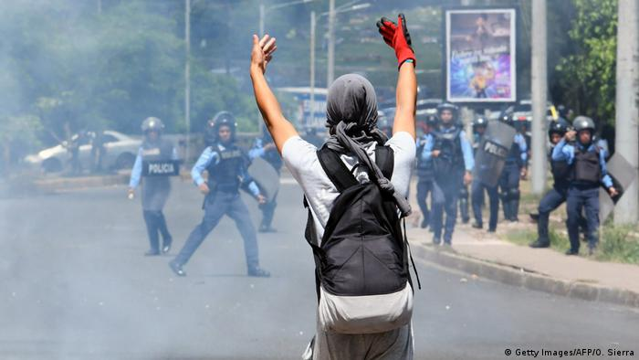 Honduras anti-government protester taunts the police