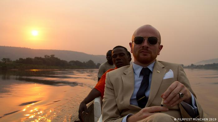 Filmstill aus THE AMBASSADOR mit Mads Brugger auf Boot in Afrika mit Besatzung