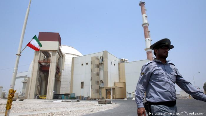 File photograph showing an Iranian security officer walking in front of the nuclear power plant in Bushehr (picture-alliance/dpa/A. Taherkenareh)
