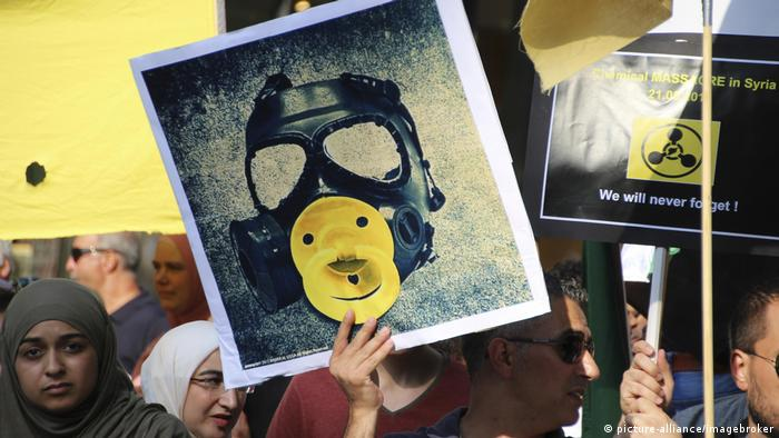 A man holds up a sign at a demonstration in Hamburg against Syrian chemical weapons attacks in Hamburg, Germany (picture-alliance/imagebroker)