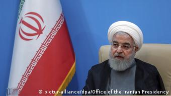 Hassan Rohani sits in front of an Iranian flag