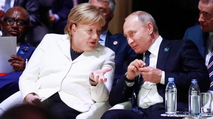 Vladimir Putin sitting next to Angela Merkel in Paris in 2018