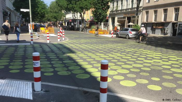 Green dots and bollards on a street
