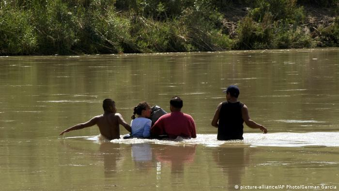 Unidentified migrants attempt to cross the Rio Grande from the state of Jalisco, Mexico to the US border