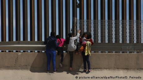 Migrants take a peek into the US city of El Paso from the Mexican city of Juarez