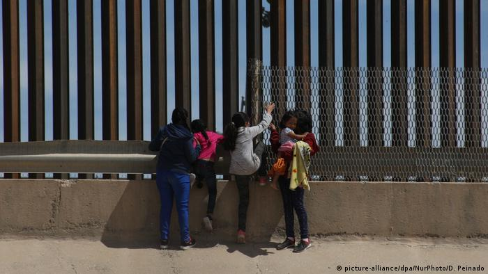 Migrants look over the border wall separating the US city of El Paso and Ciudad Juarez, Mexico.