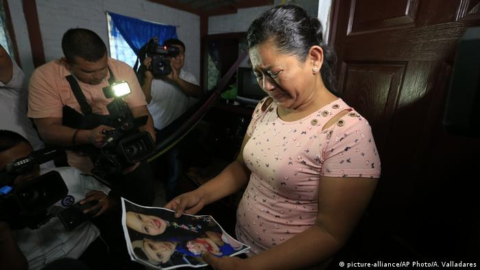 Rosa Ramirez holds a photo of her son Oscar, his wife Tania and their daughter Valeria