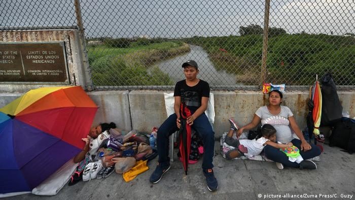 Migrants sit near the border marking at the bridge connecting Matamoros, Mexico and Brownsville, Texas.