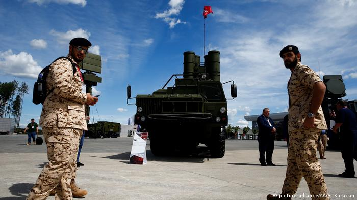 Soldiers stand in front of an S-400 aerial missile defense system