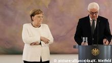 German Chancellor Angela Merkel shakes during a ceremony with German President Frank-Walter Steinmeier (picture-alliance/dpa/K. Nietfeld)