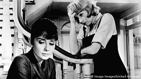 Film still The Children's Hour: two women in black and white, one seated on the stairs and the other leaning on the banister (Imago Images/United Archives)